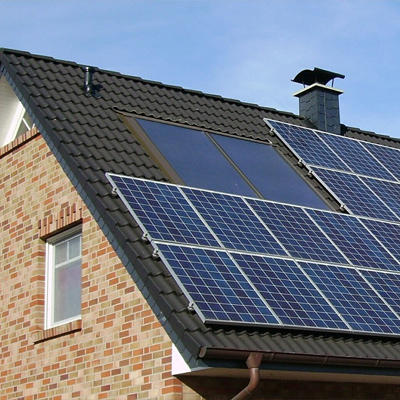 Photo of the top of a brick house with a black roof, covered in solar panels.