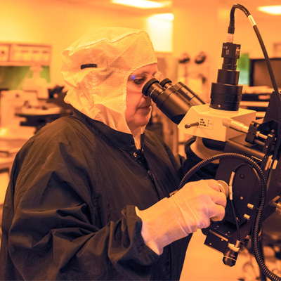 Photograph of a scientist working in a lab lit by yellow light. The scientist is wearing a protective hood, safety glasses, lab coat, and gloves, and is looking into a microscope.